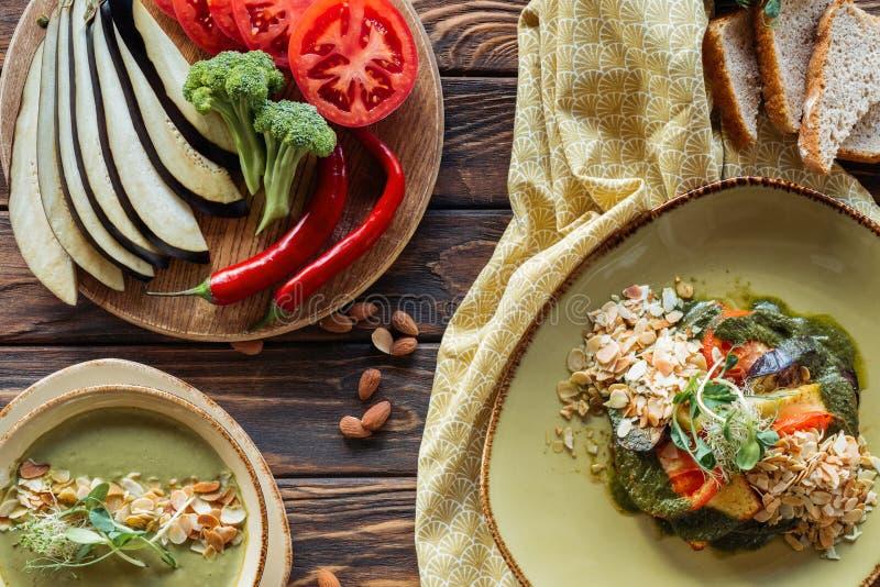 endecha plana con la ensalada vegetariana, la sopa poner crema y los ingredientes frescos dispuestos alrededor en el tablero de l foto de archivo libre de regalías