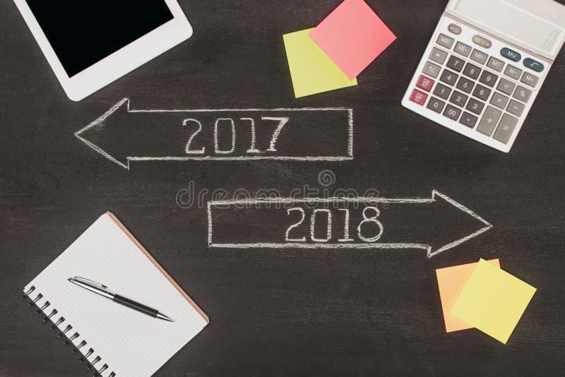 endecha plana con los materiales de oficina, flechas con 2017 y 2018 números stock de ilustración