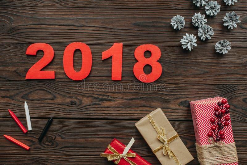 endecha plana con los regalos de la Navidad, los conos del pino y muestra de 2018 años en oscuridad ilustración del vector