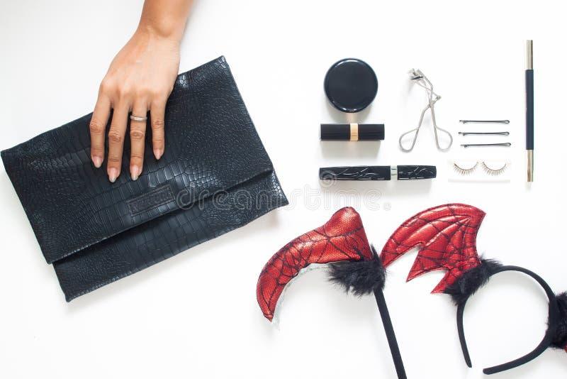 Endecha plana creativa de la mano de la mujer que sostiene el monedero de moda con los accesorios y los cosméticos del partido de imagenes de archivo