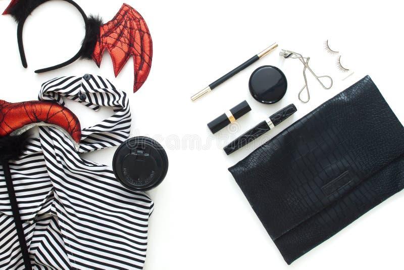 Endecha plana creativa del vestido y de los accesorios de la mujer para el partido de Halloween en el fondo blanco fotos de archivo libres de regalías