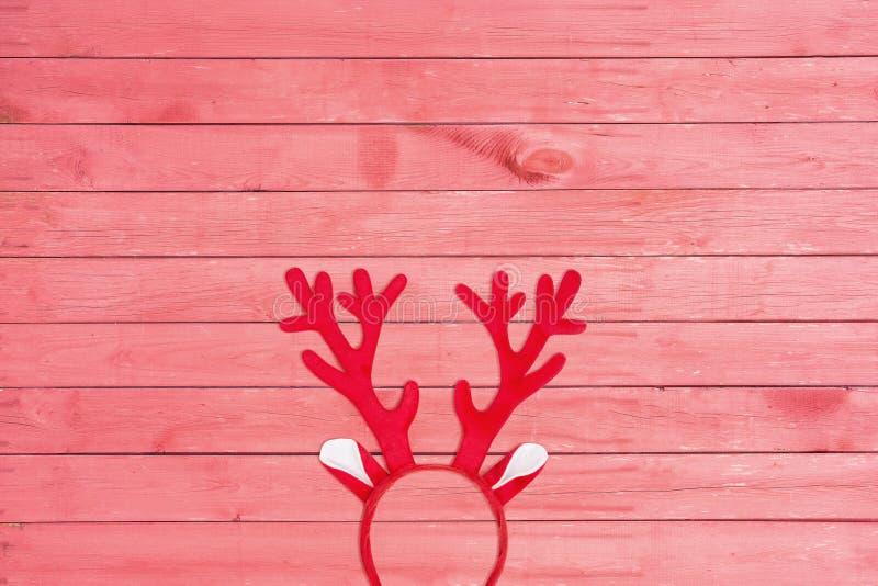 Endecha plana de astas de una venda de los ciervos en fondo de madera rosado foto de archivo libre de regalías