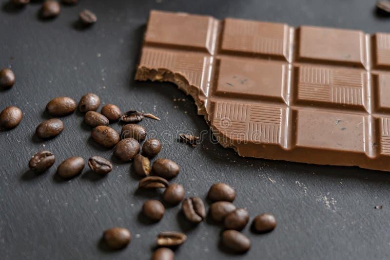 Endecha plana de la barra de chocolate mordida en la superficie oscura f imagenes de archivo