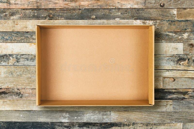 Endecha plana de la caja de cartón vacía en fondo de madera del vintage fotos de archivo