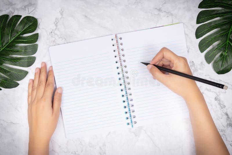 Endecha plana de la escritura de la mano de la mujer en un cuaderno en blanco de la p?gina blanca en el escritorio de m?rmol blan imágenes de archivo libres de regalías