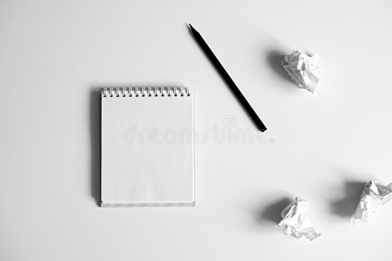 Endecha plana de la libreta blanca en blanco, del lápiz y del documento arrugado sobre el fondo blanco fotos de archivo libres de regalías