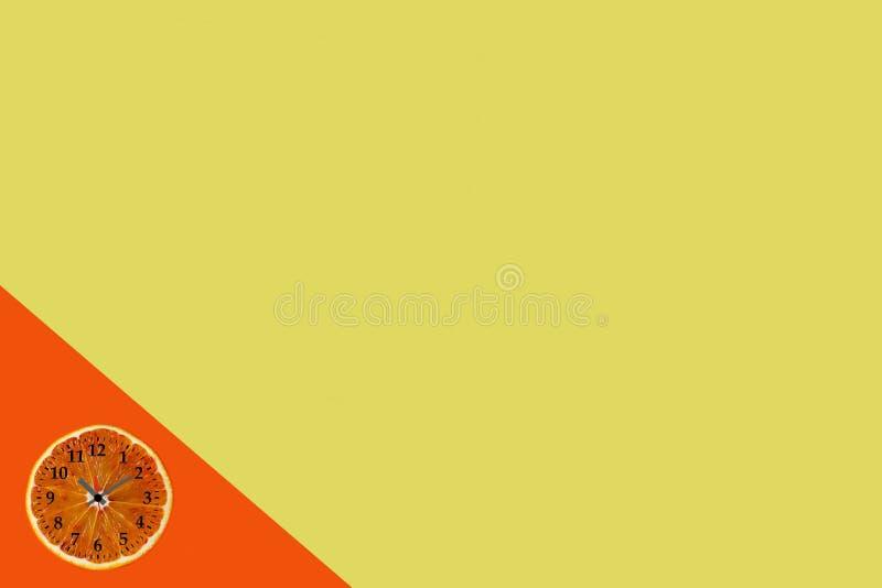 Endecha plana de la rebanada anaranjada de la fruta con el reloj en fondo de papel amarillo y anaranjado fotos de archivo