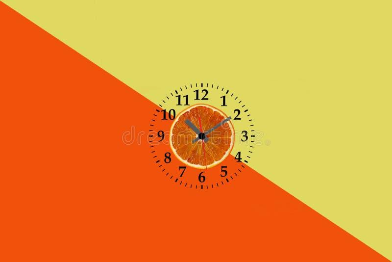 Endecha plana de la rebanada anaranjada de la fruta con el reloj en fondo de papel amarillo y anaranjado imagen de archivo libre de regalías