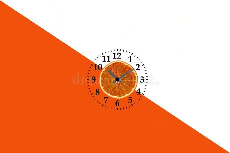 Endecha plana de la rebanada anaranjada de la fruta con el reloj en el fondo de papel blanco y anaranjado fotos de archivo