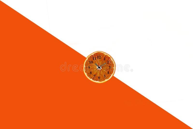 Endecha plana de la rebanada anaranjada de la fruta con el reloj en el fondo de papel blanco y anaranjado foto de archivo