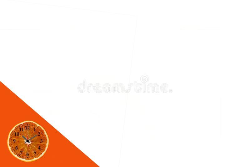 Endecha plana de la rebanada anaranjada de la fruta con el reloj en el fondo de papel blanco y anaranjado foto de archivo libre de regalías