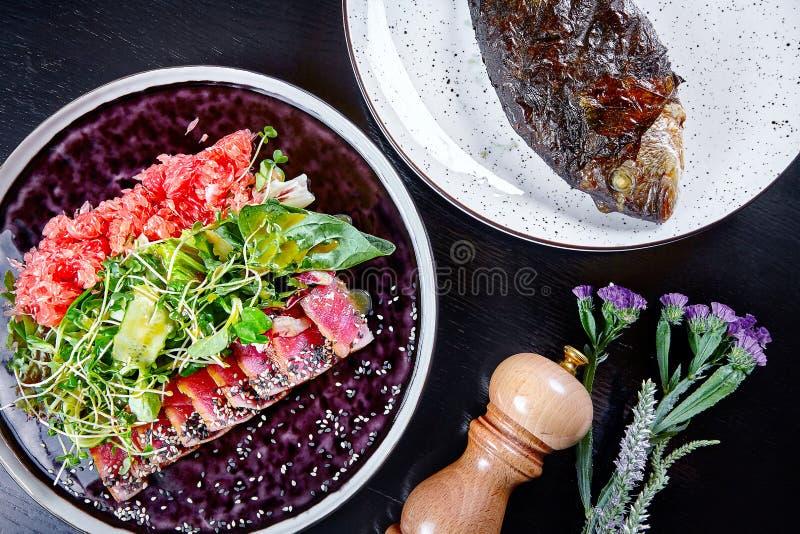 Endecha plana de la tabla de los mariscos para el almuerzo Atún asado a la parrilla con el pomelo y la ensalada verde con dorado  imagenes de archivo