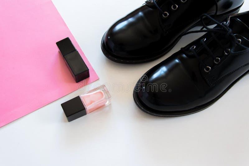 Endecha plana de la visión superior de pares clásicos de zapatos negros y de esmaltes de uñas negros y rosados imágenes de archivo libres de regalías