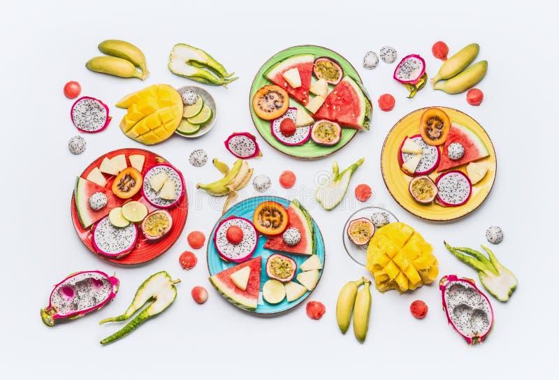 Endecha plana de las diversos frutas tropicales del verano y placas y cuencos cortados coloridos de las bayas en el fondo blanco  imagen de archivo libre de regalías