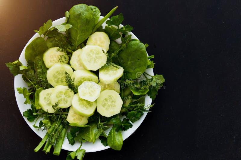 Endecha plana de las verduras verdes frescas de las hierbas eneldo, de la espinaca, de la cebolla, del perejil y del pepino en un imagenes de archivo