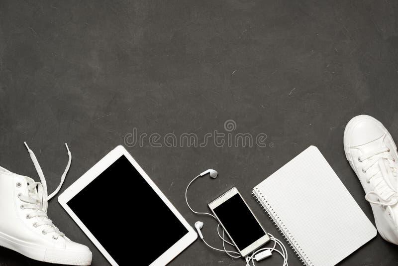 Endecha plana de las zapatillas de deporte blancas de la moda en fondo negro con el teléfono, auriculares, tableta, libro de la c imágenes de archivo libres de regalías