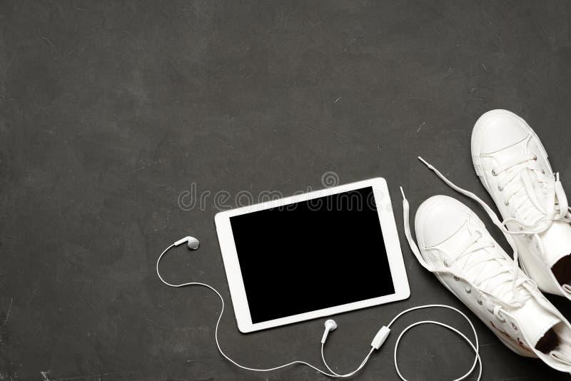 Endecha plana de las zapatillas de deporte blancas de la moda en fondo negro con el teléfono, auriculares, tableta, libro de la c fotografía de archivo