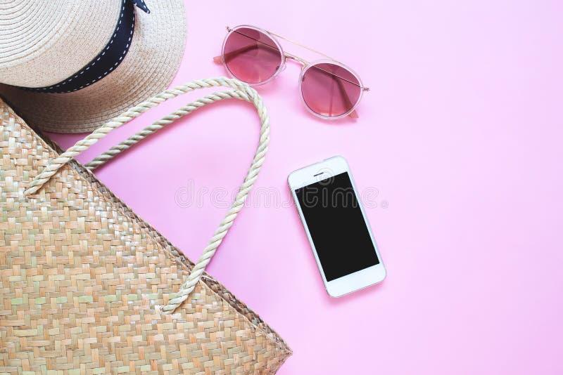 Endecha plana de los accesorios del verano con el dispositivo móvil en fondo rosado del color Moda del verano, concepto del viaje fotos de archivo libres de regalías
