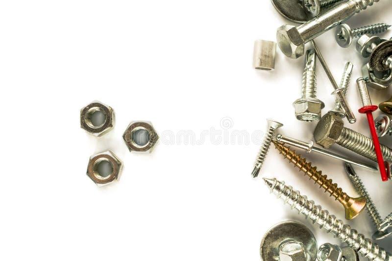 Endecha plana de nueces en blanco Tornillos de la perforación del uno mismo sujetadores Material de conexión en el fondo blanco foto de archivo
