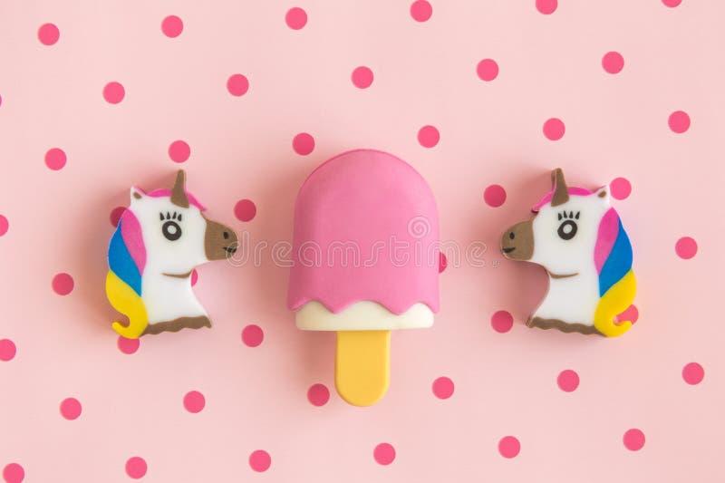 Endecha plana de unicornios y del helado en el palillo contra fondo color de rosa con los lunares imágenes de archivo libres de regalías