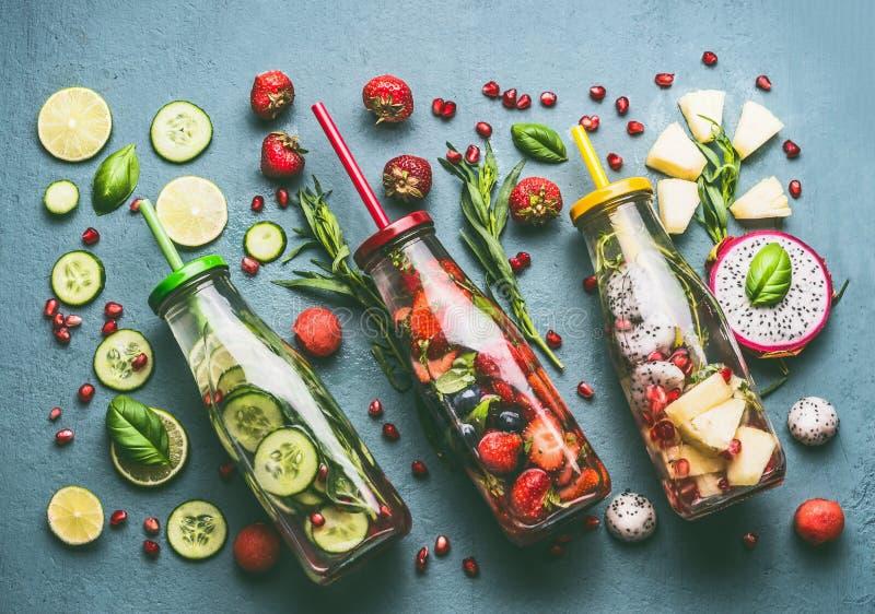 Endecha plana del agua infundida colorida en botellas con las bayas de las frutas, el pepino, las hierbas y la paja de la bebida  imágenes de archivo libres de regalías