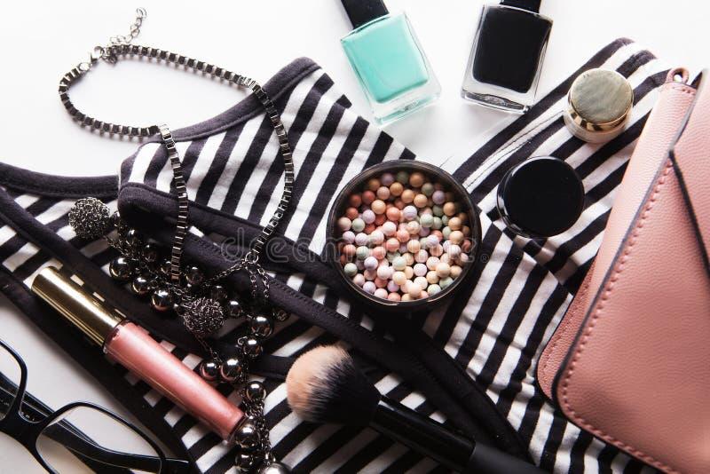 Endecha plana del bolso de cuero rosado de la mujer con los cosméticos, los accesorios y smartphone en el fondo blanco imagen de archivo