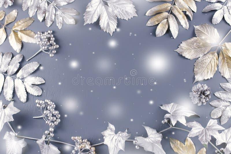 Endecha plana del concepto del invierno con las hojas de oro y de plata con caer de la nieve Fondo del marco de la Navidad libre illustration