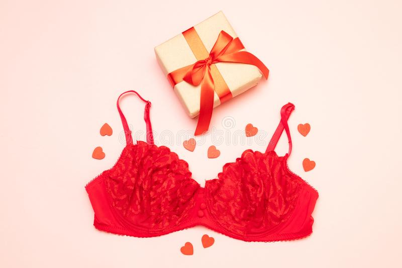 Endecha plana del regalo atractivo de la sorpresa de la ropa interior c del color rojo del cordón para mujer con la cinta roja en fotografía de archivo