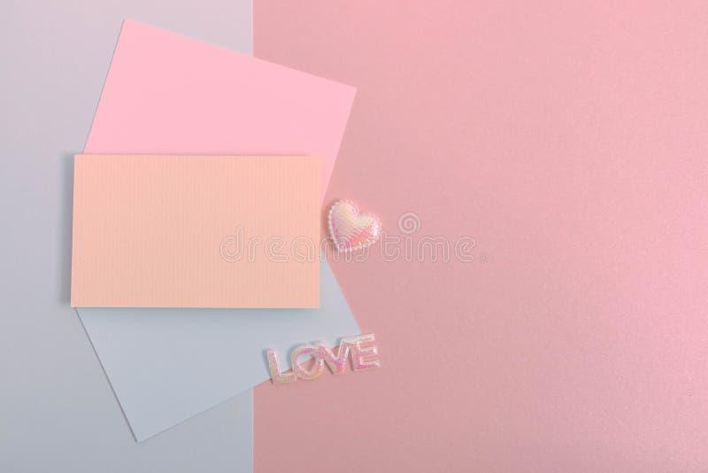 Endecha plana del sobre y de la tarjeta en colores pastel en fondo de papel hermoso fotografía de archivo