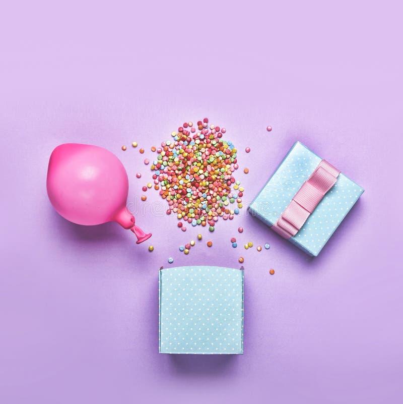 Endecha plana El estilo del minimalismo, caja de regalo azul con diverso confeti va de fiesta, los globos, decoraciones en un fon imágenes de archivo libres de regalías