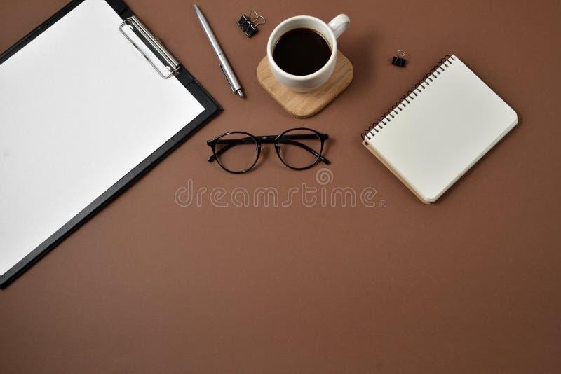 Endecha plana, escritorio de la tabla de la oficina de la visión superior Espacio de trabajo con la taza en blanco del tablero de foto de archivo libre de regalías