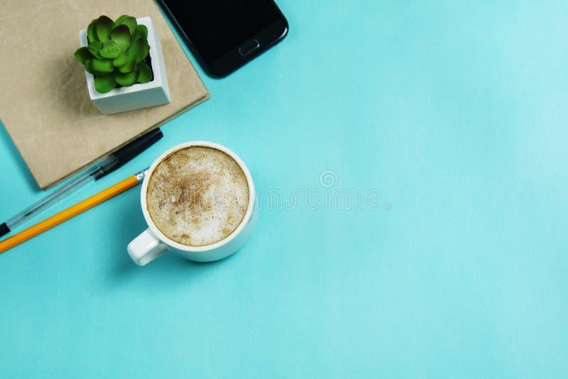 Endecha plana, escritorio de la tabla de la oficina de la visión superior Taza del smartphone, del artilugio, de los materiales d imagen de archivo