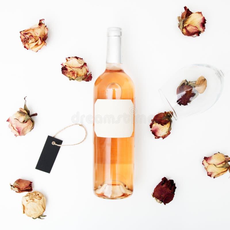 Endecha plana Estilo m?nimo Fotografía minimalista de la tendencia Una botella de rosa con una composición de rosas secadas Botel imágenes de archivo libres de regalías