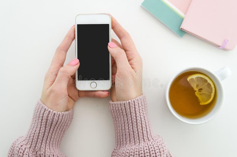Endecha plana Las manos femeninas sostienen smartphone, la taza de té con el limón y las libretas en la tabla Concepto mínimo de  foto de archivo