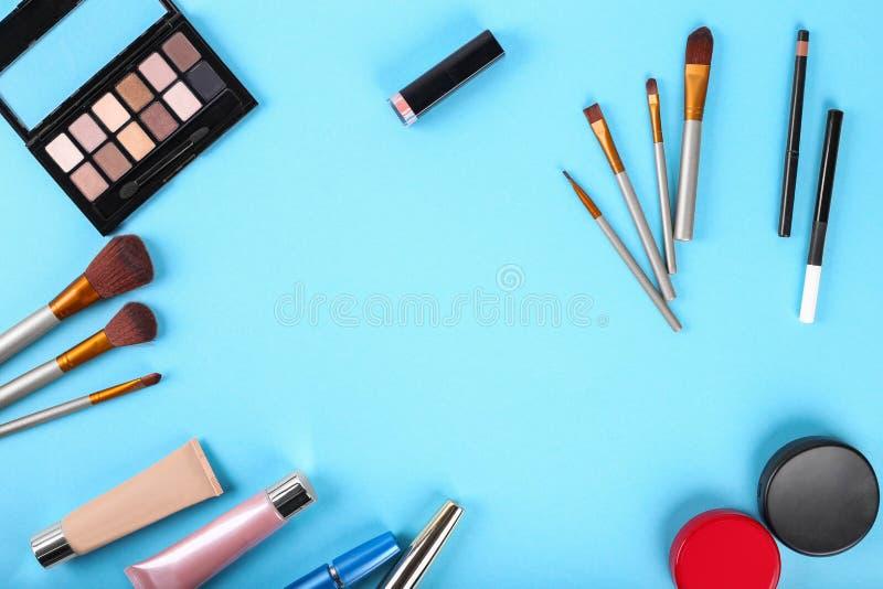 Endecha plana Paleta de sombras y de cepillos del maquillaje Polvo, lápiz corrector, highlighter, rimel, barra de labios fotografía de archivo