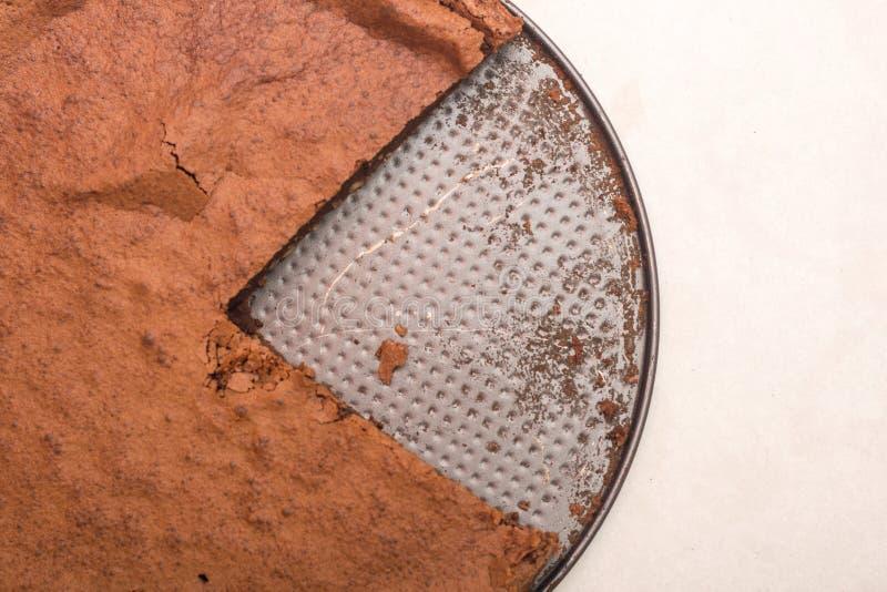 Endecha plana sobre cortado alrededor de la torta de chocolate en la bandeja de la hornada foto de archivo