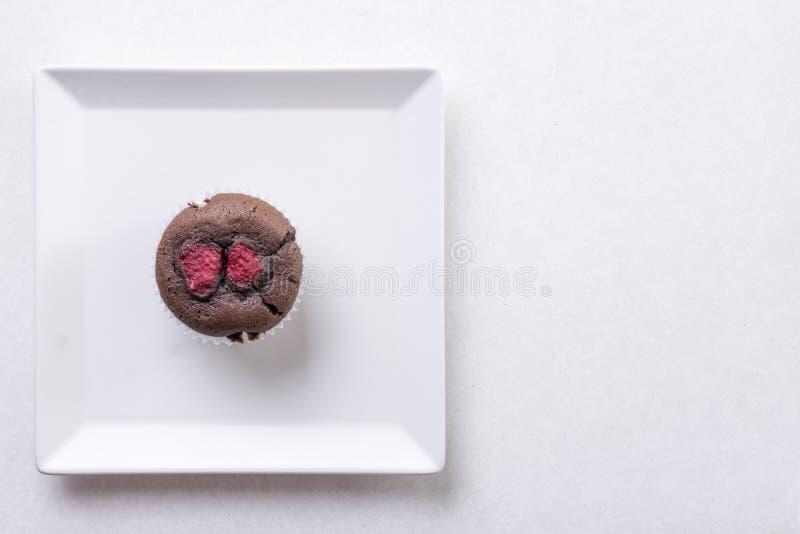 Endecha plana sobre el mollete de la torta de la taza del chocolate en la placa blanca cuadrada en el fondo de mármol blanco imagenes de archivo