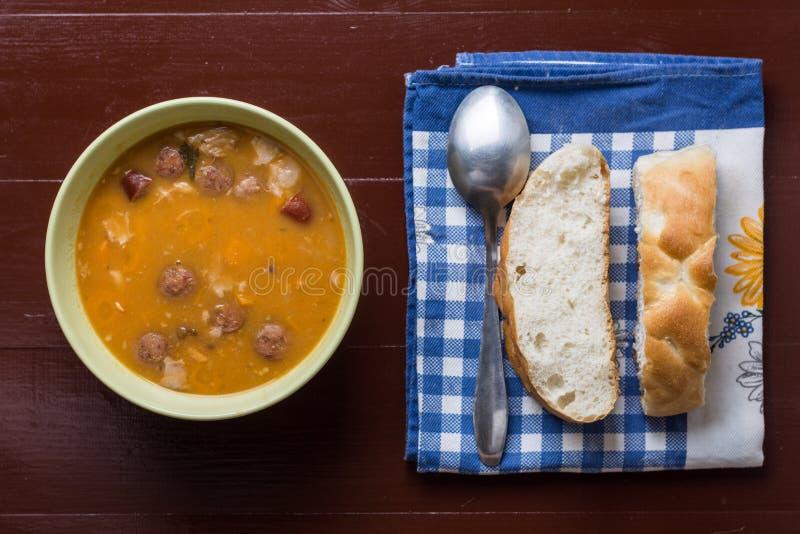 Endecha plana sobre habas cocinadas con las salchichas y el pan en el kitch fotografía de archivo