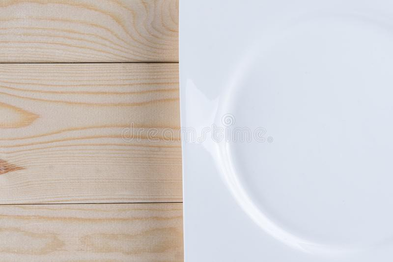 Endecha plana sobre la placa blanca vacía en la tabla de los tableros de madera con el espacio de la copia fotografía de archivo