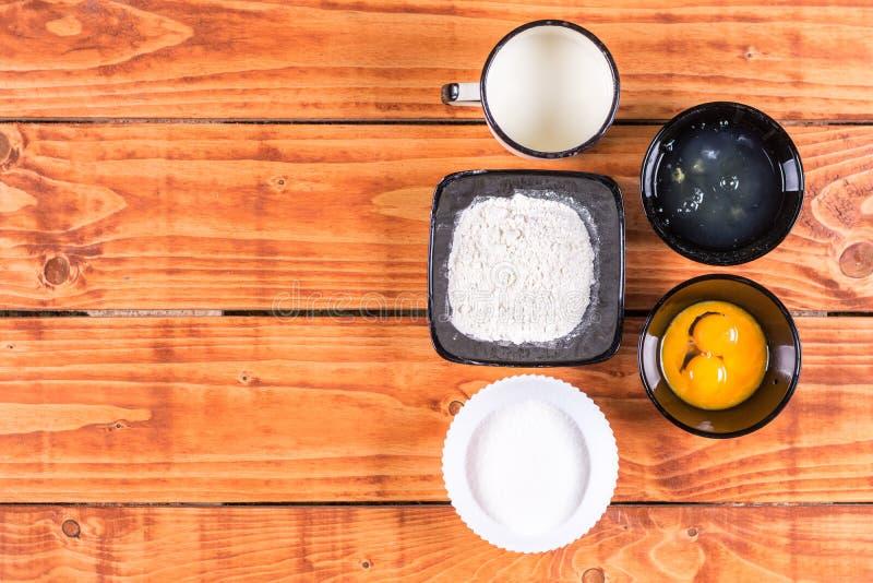 Endecha plana sobre la yema de huevo y la leche de la clara de huevo de la harina del azúcar Ingredientes para la receta american fotografía de archivo