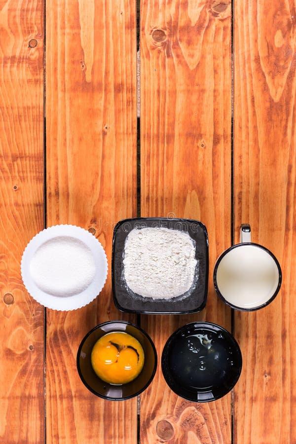Endecha plana sobre la yema de huevo y la leche de la clara de huevo de la harina del azúcar Ingredientes para la receta american imagen de archivo