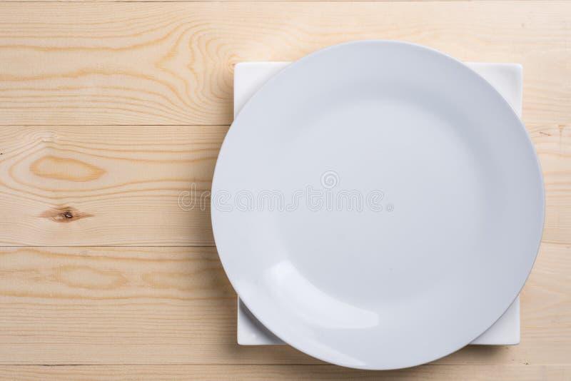Endecha plana sobre las placas blancas vacías en la tabla de madera de la textura con el espacio de la copia foto de archivo libre de regalías