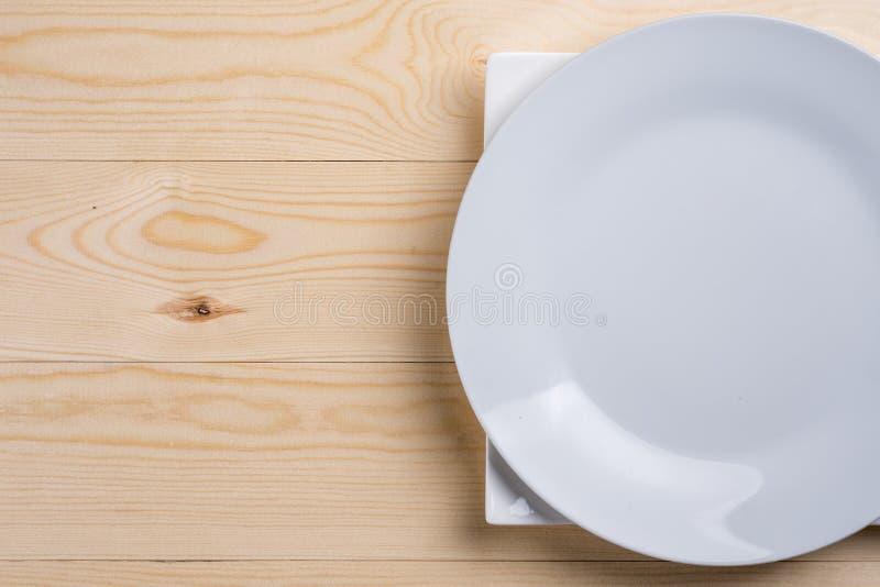 Endecha plana sobre las placas blancas vacías en la tabla de madera de la textura con el espacio de la copia imagenes de archivo