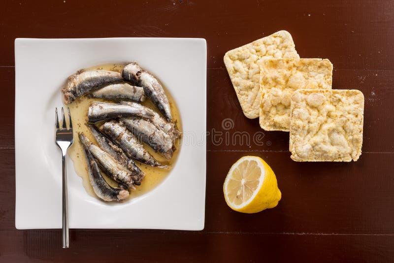 Endecha plana sobre las sardinas adobadas en el aceite con pan del limón y de maíz imagen de archivo