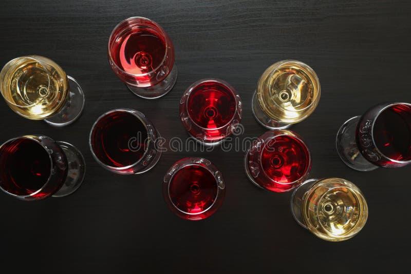 Endecha plana. Vidrios con diferentes vinos de fondo oscuro fotos de archivo