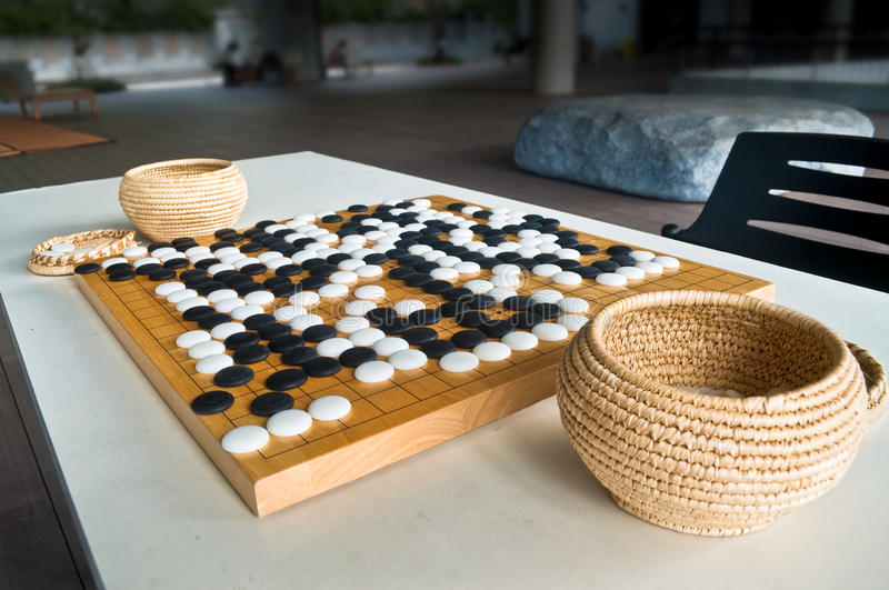 Ended game Go board. Ended Go game on wooden board played with Chinese style stone pieces, stones with curve on one side and flat on the other side stock photos