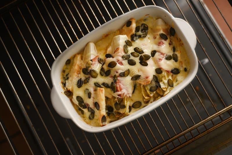 Endibias o gratén de la achicoria con las semillas de la manzana, del jamón, del queso y de calabaza en una cazuela en una rejill fotos de archivo