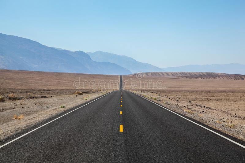Endless and lonely blacktop road going into the mountain range entering Death Valley National Park. Endless and lonely blacktop road going off into the horizon royalty free stock images