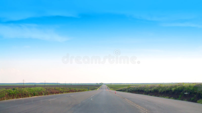 Endless road. In green field and blue sky stock images