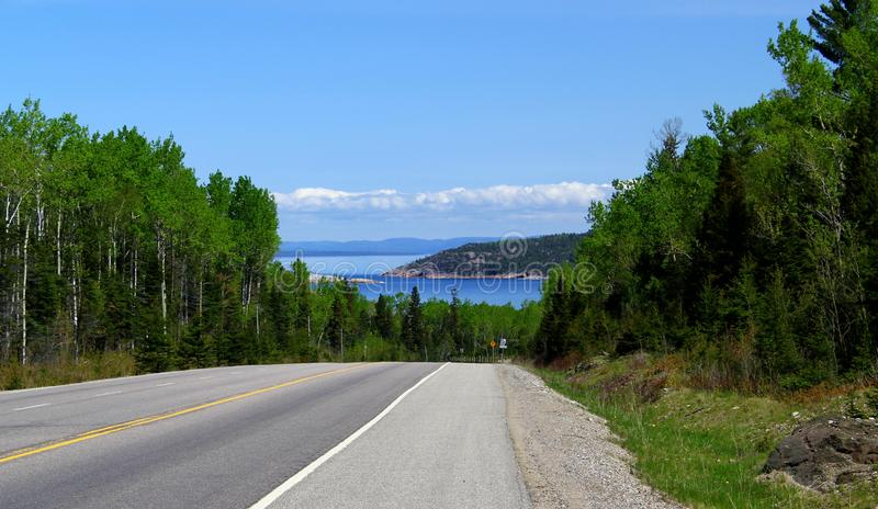 Endless road - Road leads through beautiful rural farm land - horizontal framed shot. Endless road / beautiful blue sky / USA / Canada Endless road - Road leads royalty free stock photos